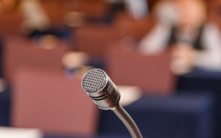 microphone-over-conference-hall-background-LF8S9VR