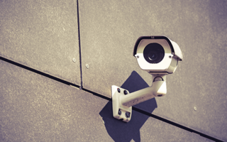 security-camera-on-gray-office-building-wall-PH7WVF9